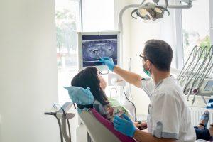 dentysta pokazujący zdjęcie rentgenowskie szczeki pacjentowi siedzącemu na fotelu